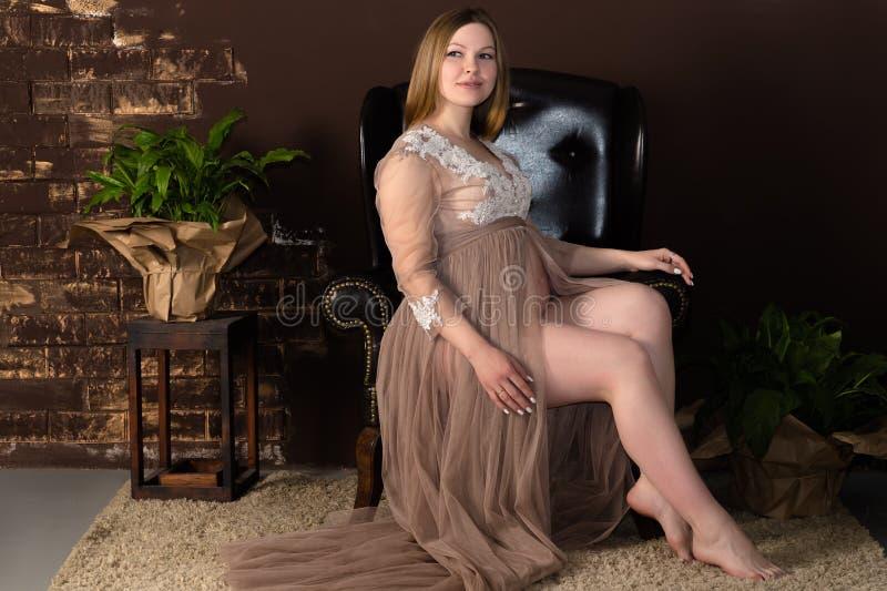 Charmante zwangere vrouwenzitting op de stoel stock foto's