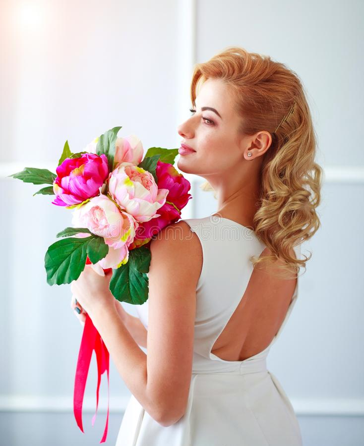 Charme de la jeune mari?e heureuse et joyeuse de jeune femme dans la robe blanche avec le bouquet des fleurs dans le studio image libre de droits