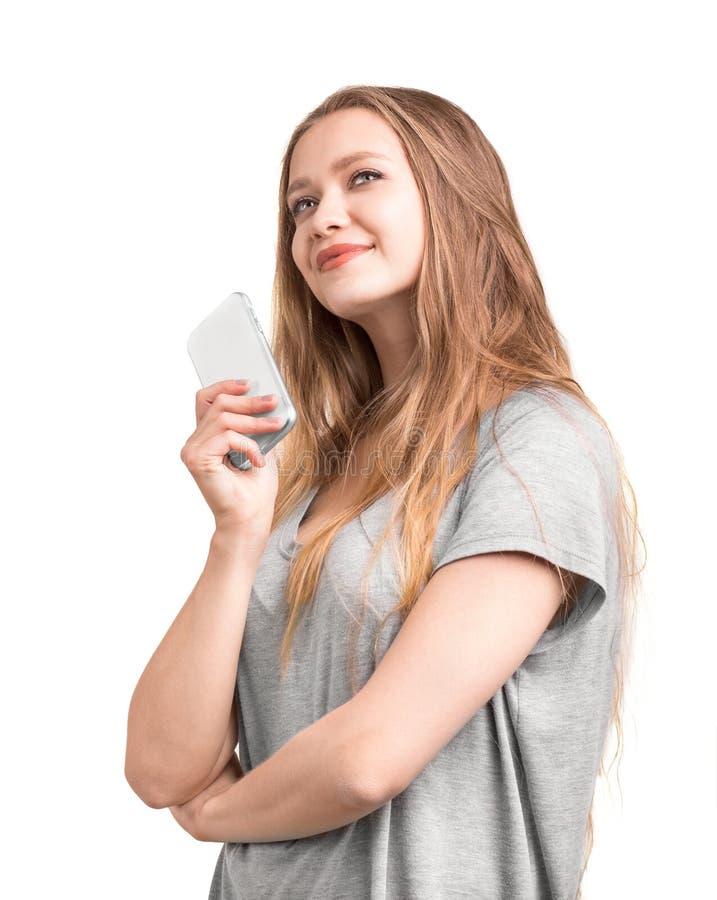 Charme et fille assez jeune avec de longs et blonds cheveux avec un téléphone portable, d'isolement sur un fond blanc photos libres de droits