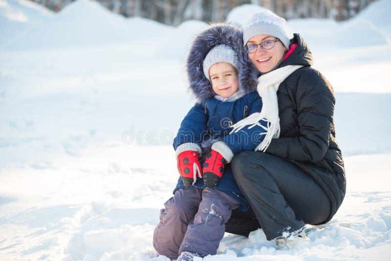 Charmerande liten flicka som klumpar ihop med sin positiva mamma arkivfoton