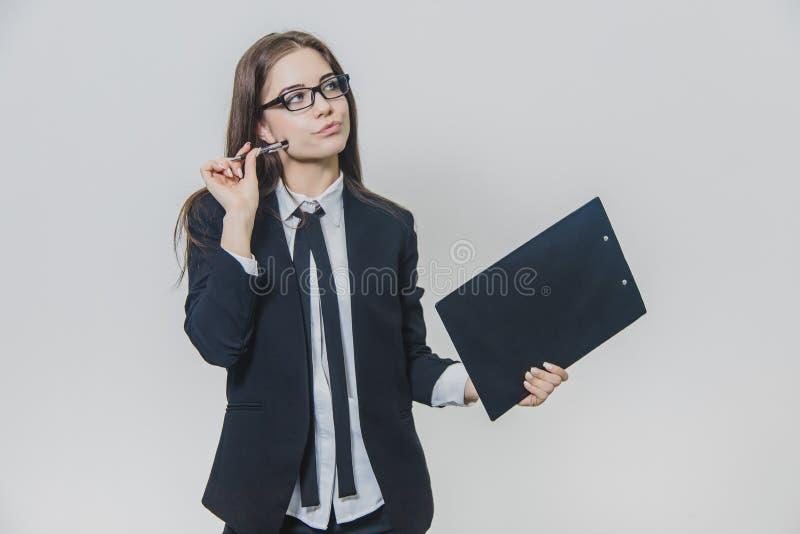 Charmeren van Kaukasische bedrijfsvrouw houdt zwart document houder of klembord en kijkt opzij denkend over haar plan royalty-vrije stock afbeeldingen