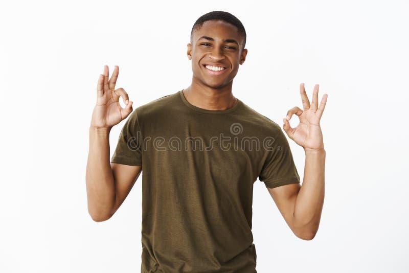 Charmerend assertieve en vriendschappelijke Afrikaanse Amerikaanse vriend die o.k. gebaren met beide handen tonen als het verzeke royalty-vrije stock afbeelding