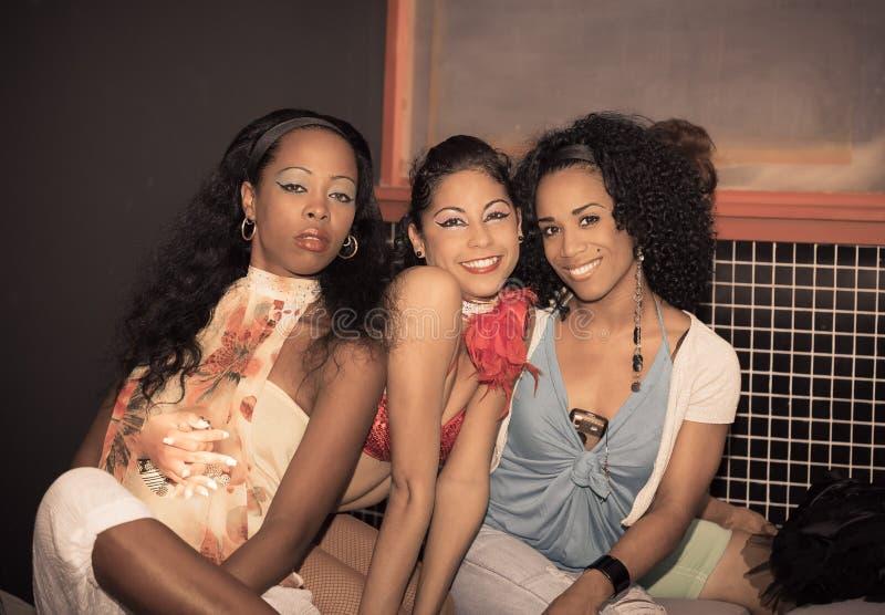 Charmerend de gelukkige Cubaanse meisjes die van het vermaakteam en zitten ontspannen na toon prestaties royalty-vrije stock foto's