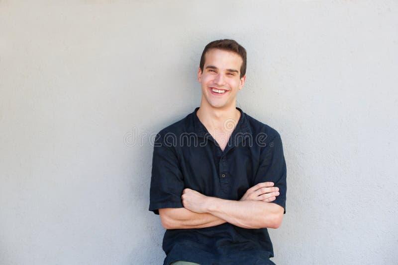 Charmerend de jonge mens die met gekruiste wapens glimlachen royalty-vrije stock afbeeldingen