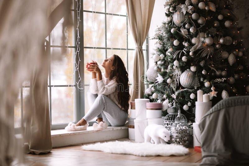 Charmerend donker-haired meisje gekleed in broek, houden de sweater en de warme pantoffels een rode kopzitting op de vensterbank  royalty-vrije stock afbeelding