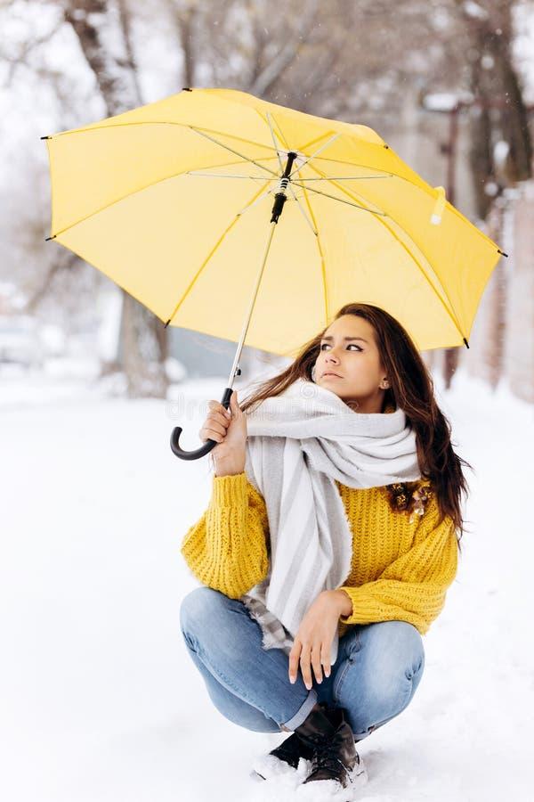 Charmerend donker-haired meisje gekleed in een gele sweater, zitten de jeans en een witte sjaal op weg onder het geel royalty-vrije stock foto