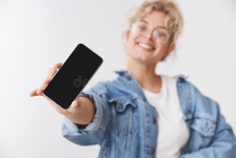 Charmerend gelukkig knap geactiveerd jong blond Kaukasisch meisje vaag achter rekhand toon camerasmartphone stock fotografie