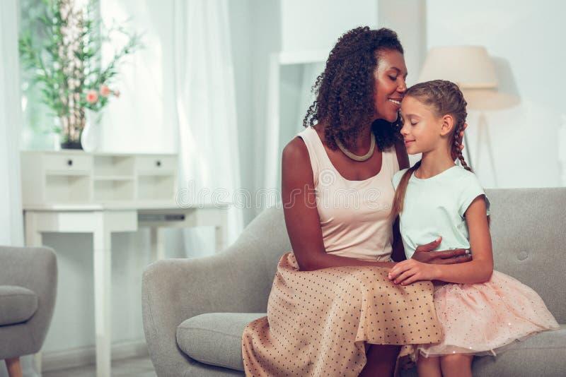 Charmerend houdende van Afro-Amerikaanse moeder die teder vrij zoete kleine dochter koesteren stock foto's