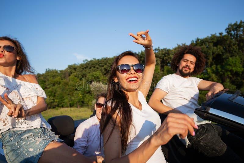 Charmerend jong donkerharige in zonnebril met vrienden zitten in zwarte cabriolet op een zonnige dag royalty-vrije stock fotografie