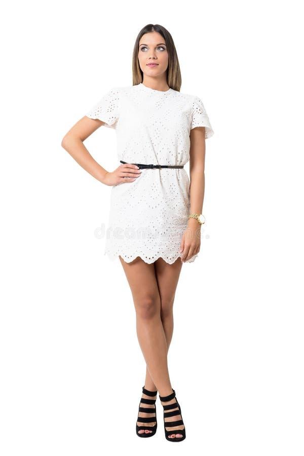 Charmerend jonge dame die in stiletto en witte kleding omhoog kijken royalty-vrije stock foto's