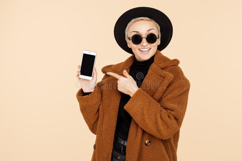 Charmerend jonge hipstervrouw met blonde kort haar die een laag dragen, richten de hoed en de zonnebril vinger op smartphone stock afbeelding