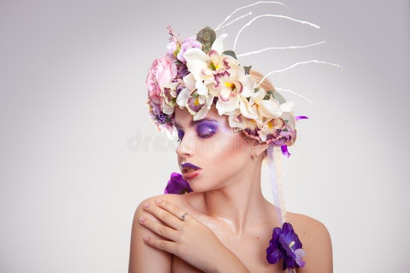 Charmerend jonge vrouw die met bloemen weg kijken stock afbeeldingen