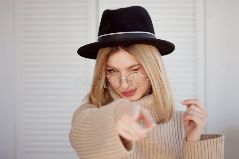 Charmerend jonge vrouw in een zachte sweater en glazen, in een zwarte vilten hoed royalty-vrije stock afbeeldingen