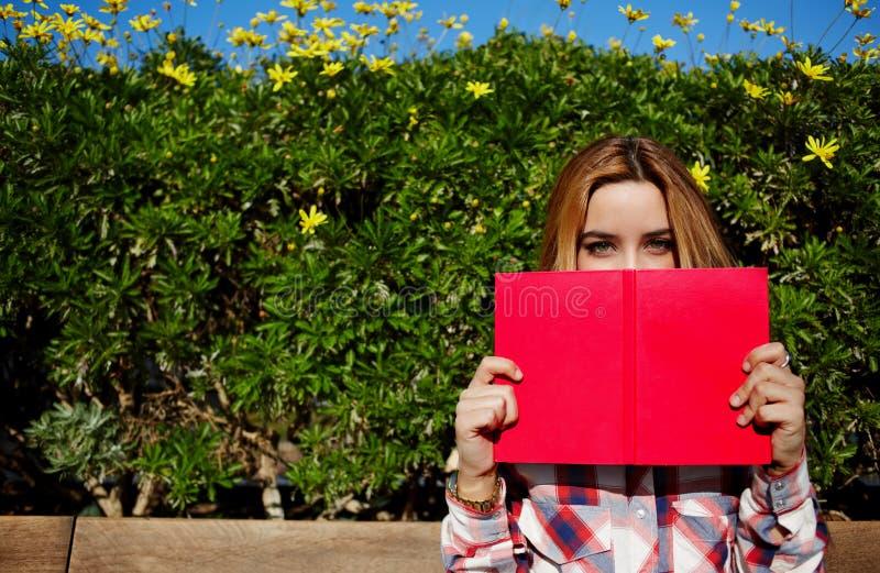 Charmerend jonge vrouw met roze die boek dicht bij haar gezicht wordt gesteund royalty-vrije stock afbeelding