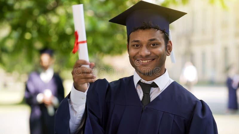 Charmerend Spaanse gediplomeerde die en diploma voor camera, succes glimlachen tonen stock afbeelding
