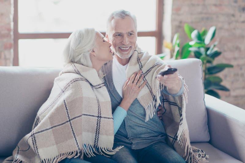 Charmerend twee bejaarde mensen zitten op een laag thuis resti stock fotografie