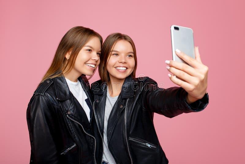 Charmerend twee jonge tweelingzusters in leerjasjes met heldere glimlach gebruik smartphone over roze achtergrond Tweeling zuster royalty-vrije stock afbeelding
