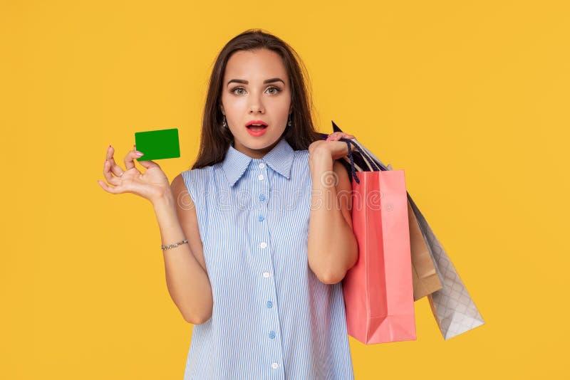 Charmerend vrij aantrekkelijk sexy meisje die creditcard tonen en vele kleurrijke pakketten in hand houden, is het comfortabel stock afbeelding