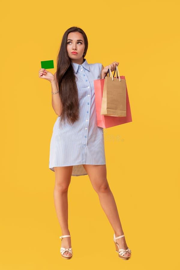 Charmerend vrij aantrekkelijk sexy meisje die creditcard tonen en vele kleurrijke pakketten in hand houden, is het comfortabel royalty-vrije stock afbeelding