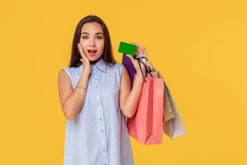 Charmerend vrij aantrekkelijk sexy meisje die creditcard tonen en vele kleurrijke pakketten in hand houden, is het comfortabel royalty-vrije stock afbeeldingen
