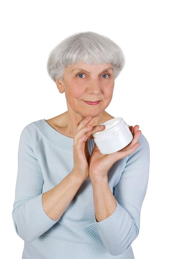 Charmig äldre kvinna som applicerar skönhetsmedelkräm på hennes framsida för ansikts- hudomsorg på en vit bakgrund royaltyfri foto