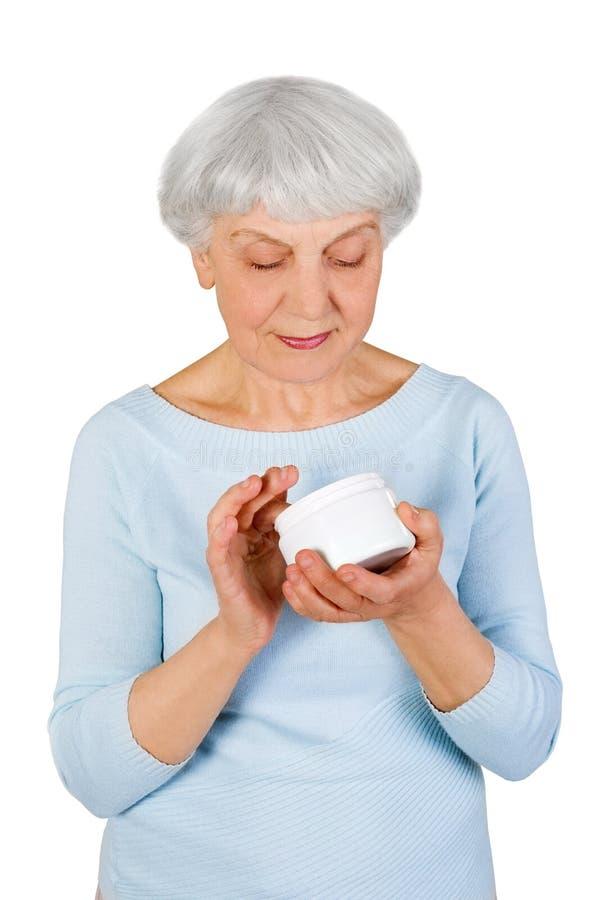 Charmig äldre kvinna som applicerar skönhetsmedelkräm på hennes framsida för ansikts- hudomsorg på en vit bakgrund royaltyfri bild