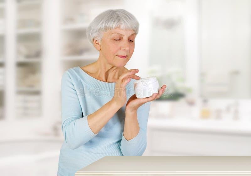 Charmig äldre kvinna som hemma applicerar skönhetsmedelkräm på hennes framsida för ansikts- hudomsorg i badrum arkivbild