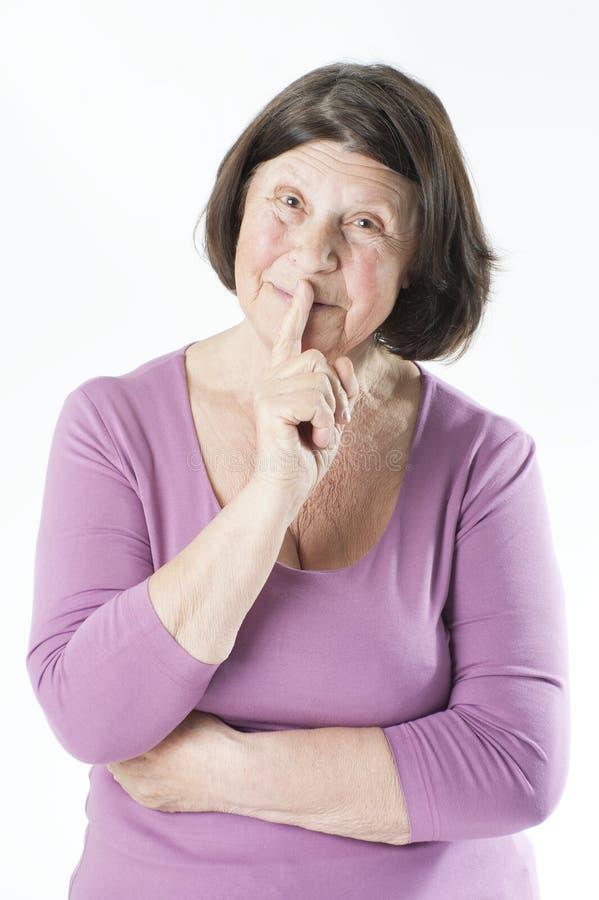 Charmig äldre kvinna som rymmer ett finger till hennes mun (en gest arkivfoto