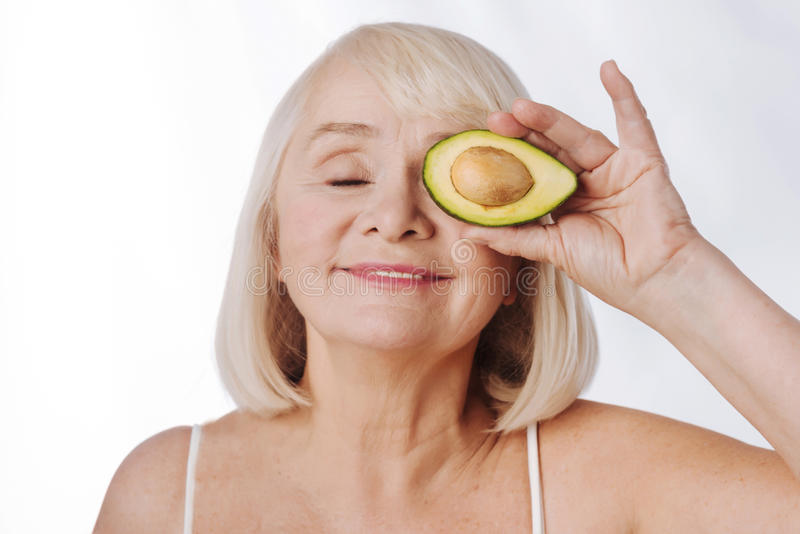 Charmig angenäm kvinna som rymmer en avokado halv nära ögat arkivbild