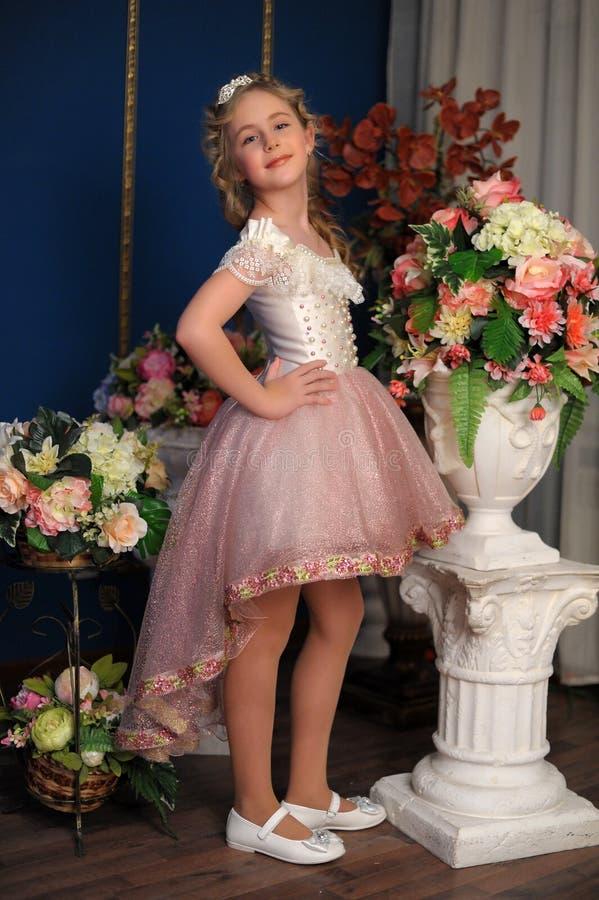 Charmig blond flicka i en vit klänning med en persika royaltyfri bild