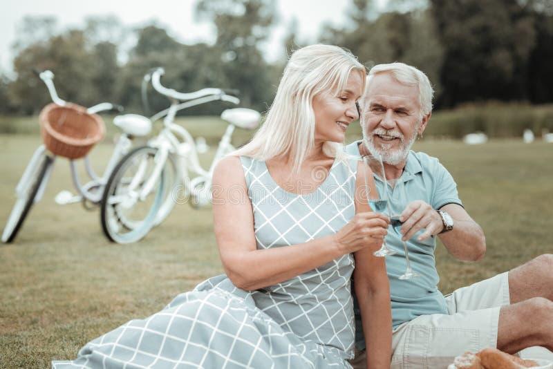 Charmig blond kvinnabenägenhet på hennes man royaltyfri bild