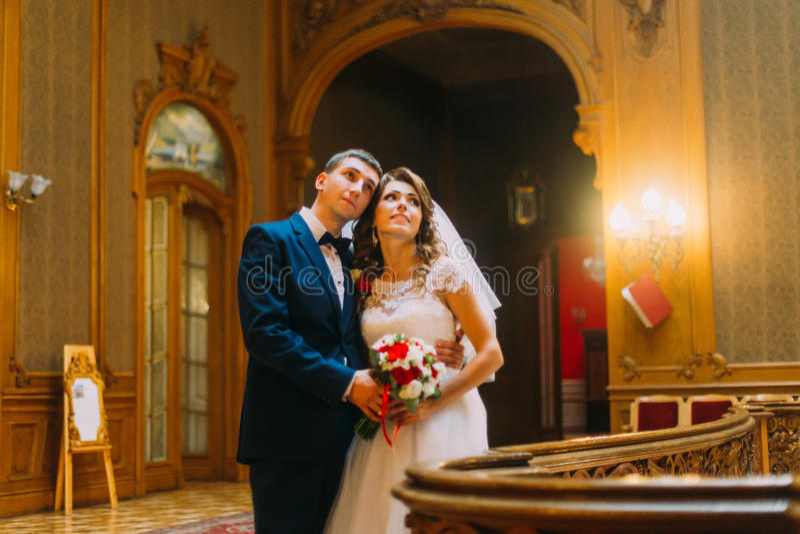 Charmig brud och stilig elegant brudgum som poserar nära gammal träbaluster med bakgrunden av den lyxiga inre fotografering för bildbyråer
