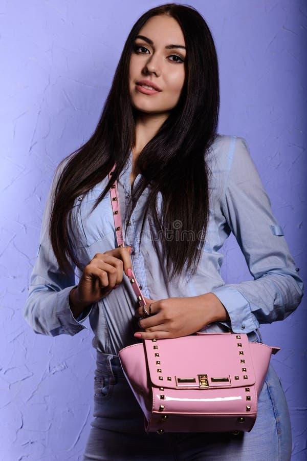 Charmig brunett med långt hår som rymmer en rosa handväska arkivbild