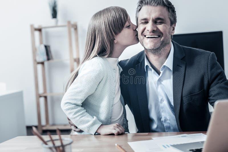 Charmig dotter som kysser hennes pappakind arkivbild