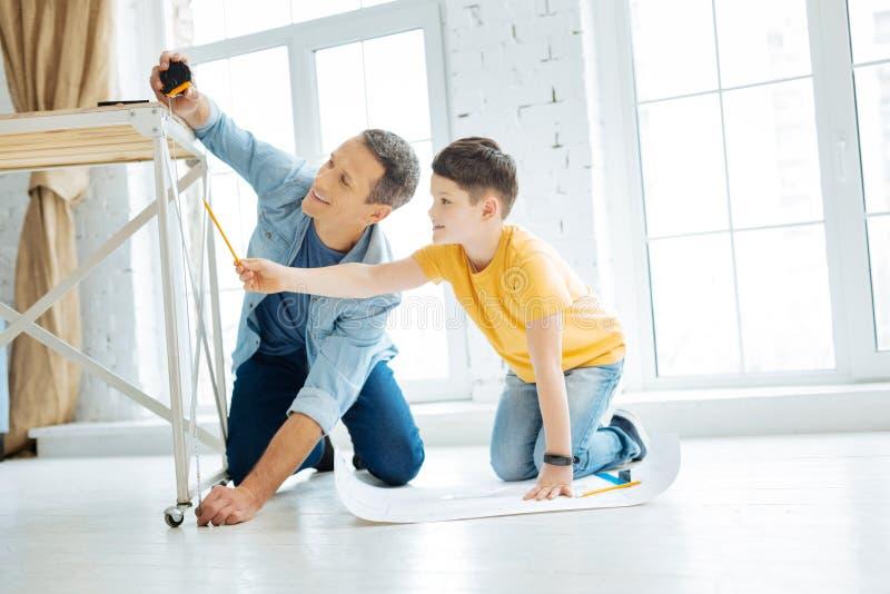 Charmig fader och son som arbetar på tabellkonstruktion royaltyfri bild