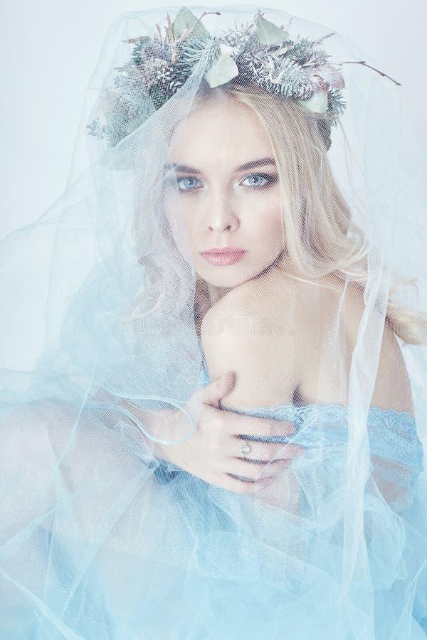Charmig felik kvinna i en blå eterisk klänning och en krans på hennes huvud på vit bakgrund, försiktig mystisk blond flicka arkivbild