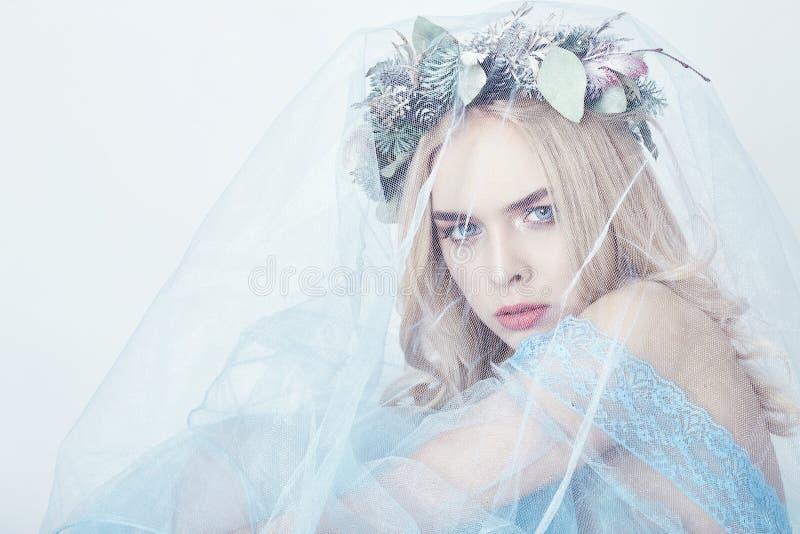 Charmig felik kvinna i en blå eterisk klänning och en krans på hennes huvud på vit bakgrund, försiktig mystisk blond flicka royaltyfri bild