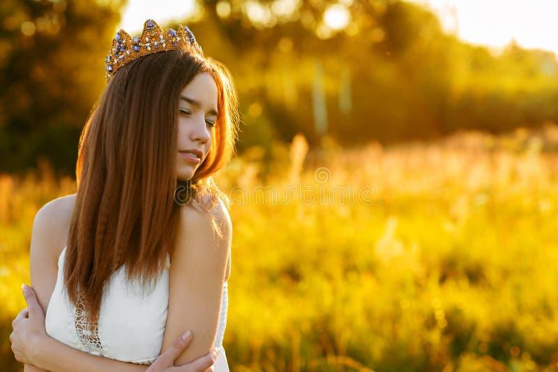 Charmig flicka med en krona utomhus royaltyfria foton