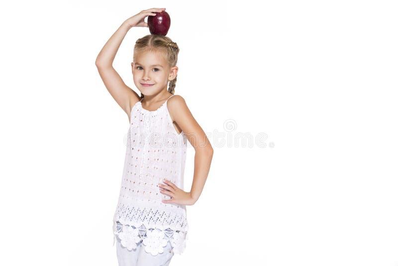 Charmig flicka med ett äpple fotografering för bildbyråer