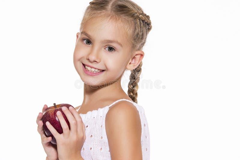 Charmig flicka med ett äpple royaltyfria bilder
