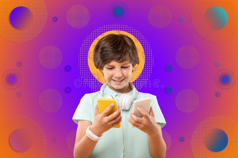 Charmig glad pojke som jämför telefoner på bakgrund arkivbild