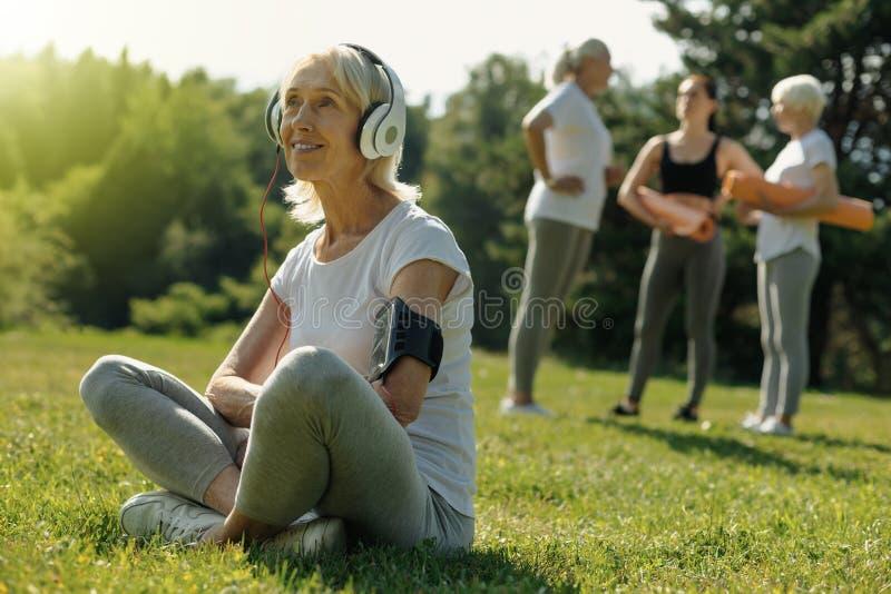 Charmig hög kvinna som ler, medan lyssna till musik royaltyfri bild