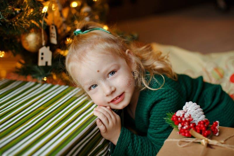 Charmig knubbig liten blond flickaliten flicka i en grön klänning royaltyfri foto