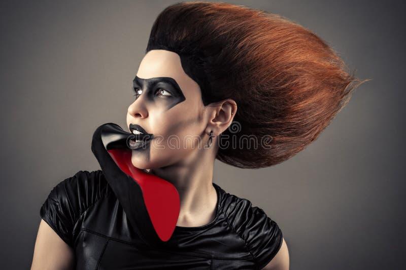 Charmig kvinna med en mörk makeup och frodig frisyr med hälet i mun royaltyfri fotografi