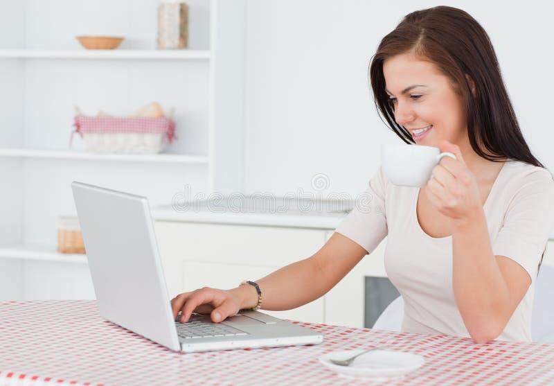 Charmig kvinna som använder henne bärbar dator och har en tea arkivbild