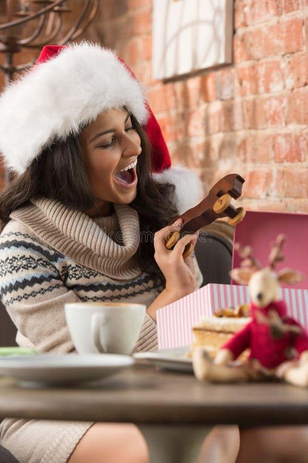 Charmig kvinna som bär gåvan för jul för Santa Claus hattöppning arkivfoto