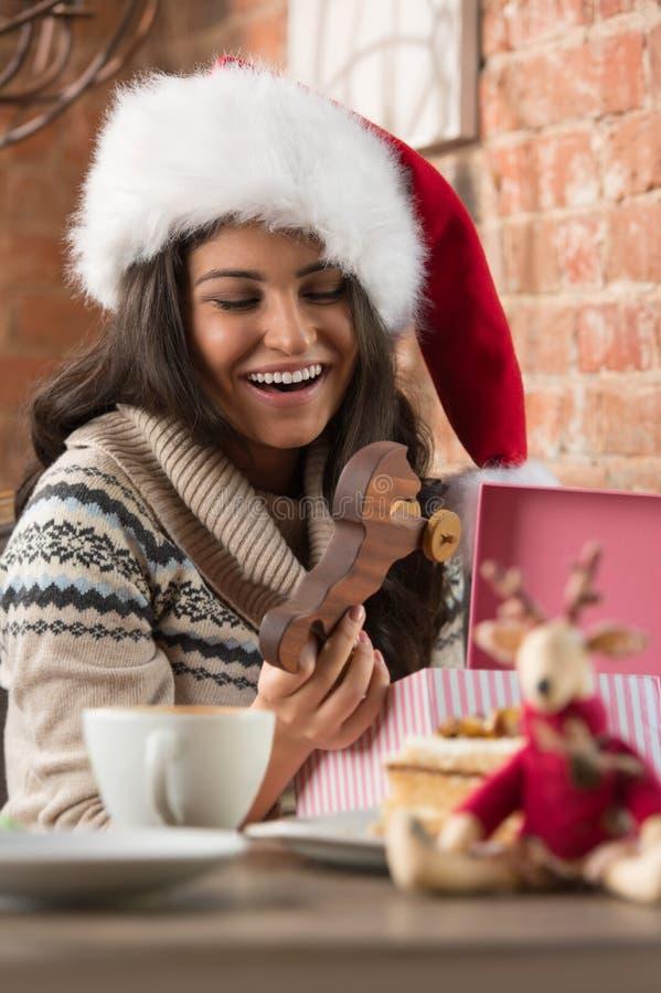 Charmig kvinna som bär gåvan för jul för Santa Claus hattöppning fotografering för bildbyråer