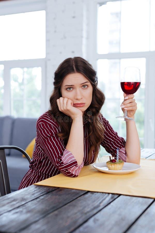 Charmig kvinna som känner sig ensam vänta på hennes man i restaurang arkivbilder