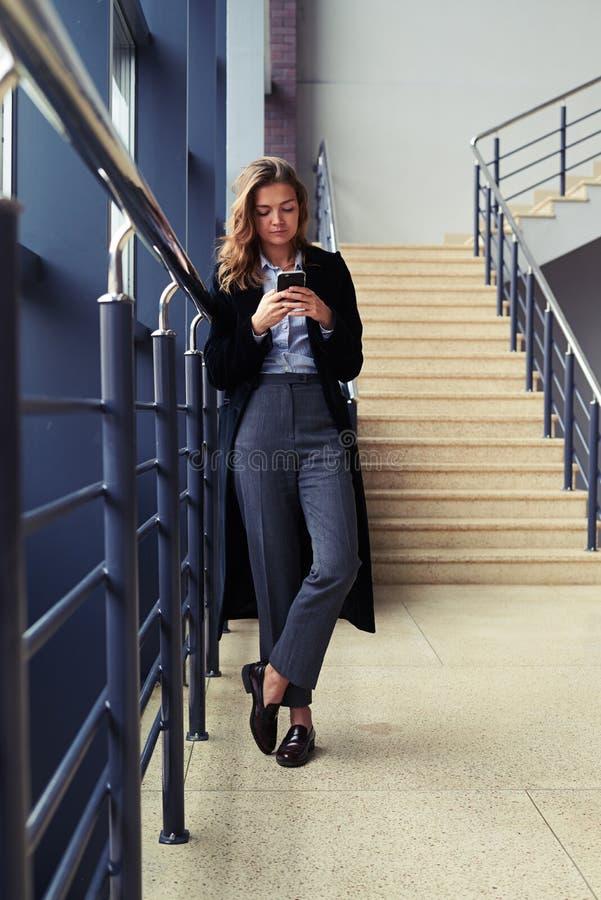 Charmig kvinnlig med moderiktig blick genom att använda telefonen royaltyfri foto