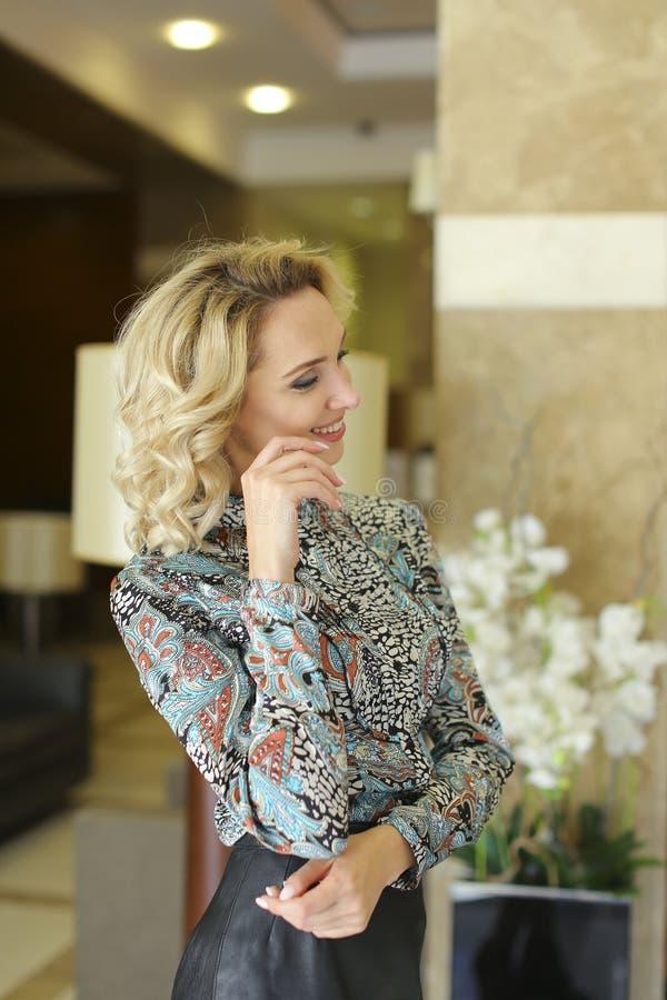 Charmig kvinnlig person i den läderkjolen och blusen som inom står nära blommor arkivfoton